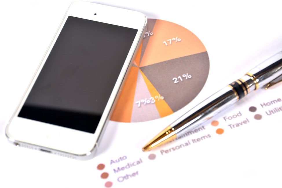 Cellphone and a pen on a paper with pie chart budget