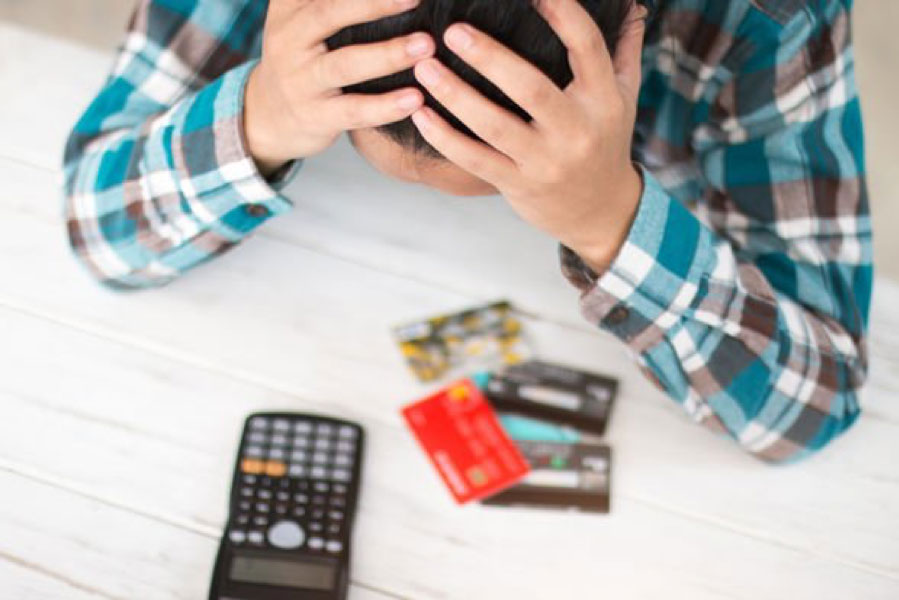 A person looking distressed while staring at pile of credit cards in front of him
