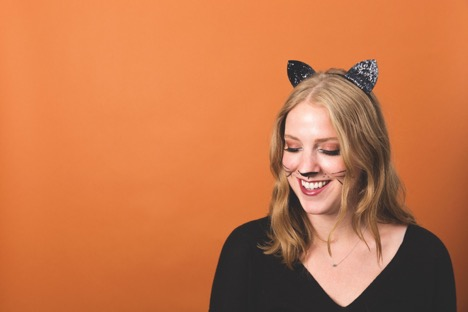 blonde woman in cat ears with face paint smiling in front of orange background