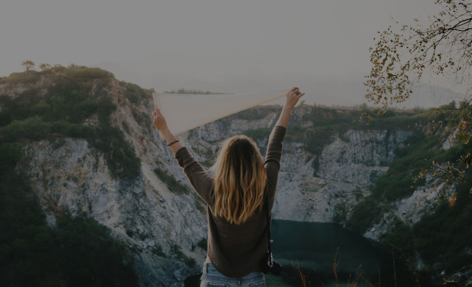 Girl standing on a top of a mountain with hands raised to celebrate her achievement