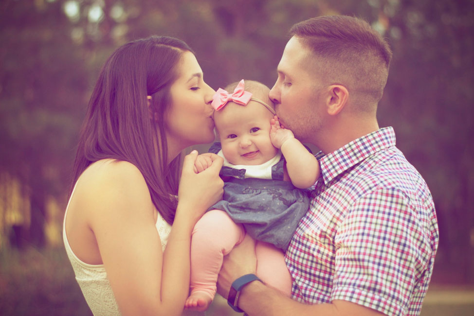 Couple kissing their infant daughter