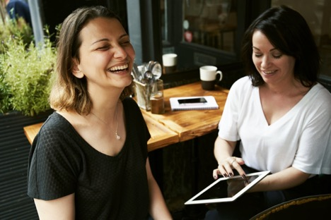 woman laughing on right next to a smiling woman on left holding an iPad next to a wooden table