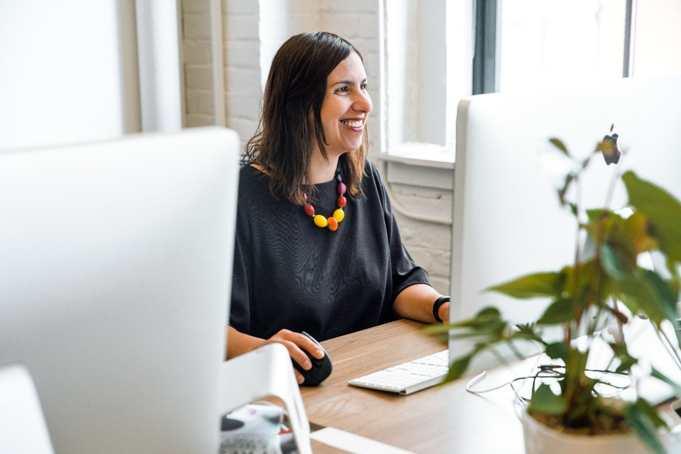 Smiling woman sitting in front of computer looking at short term online loans