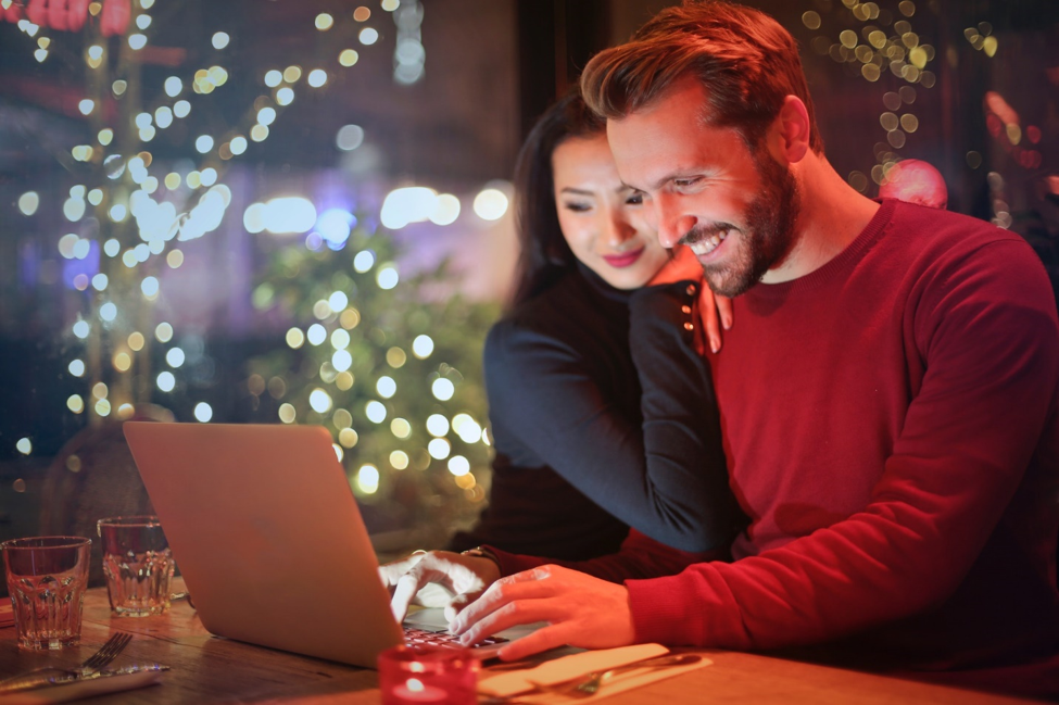 man and woman sitting next to each other in front of open laptop on table in front window at nighttime